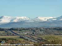 View of Pentre Berw with snow on the mountains.